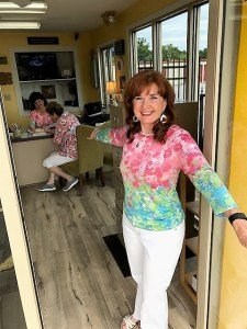 Owner Sophrona Chapman holds office door open and gestures to come in